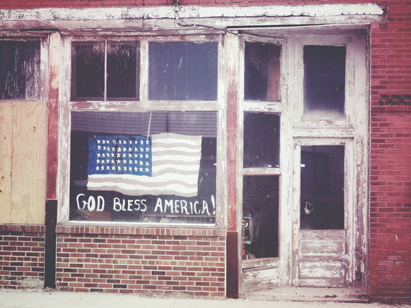 Run-down storefront with american flag painted in window.